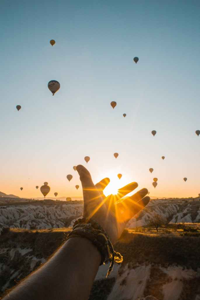 photo of person s hand across flying hot air balloons during golden hour